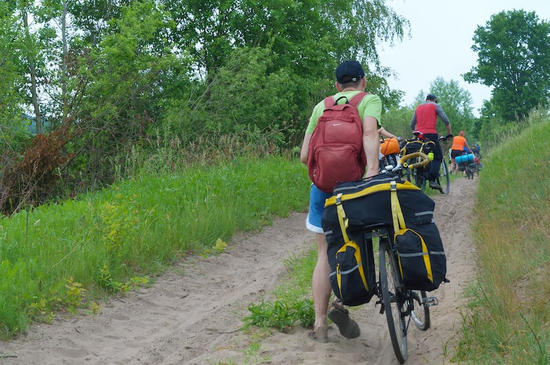 Cyclist wheeling bike up hill with loaded trunk