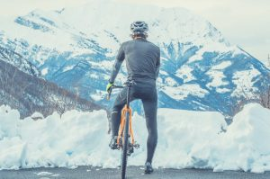 Cyclist Standing In The Snow With Helmet On