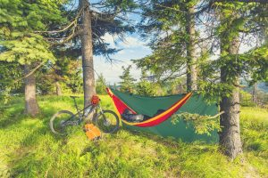 Camping with hammock in summer woods whilst bikepacking