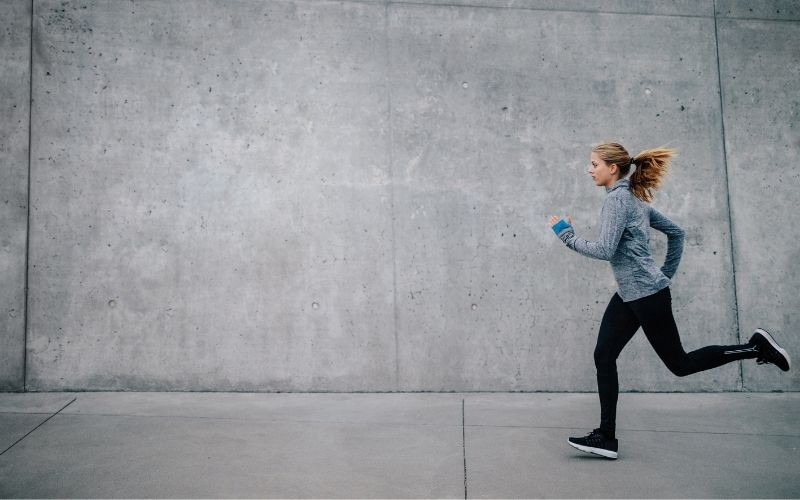 Female Running Along Concrete Wall