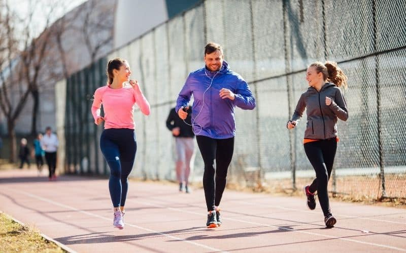 Group of runners along track laughing