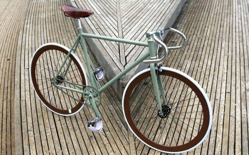 Green fixie bike with brown and white wheels