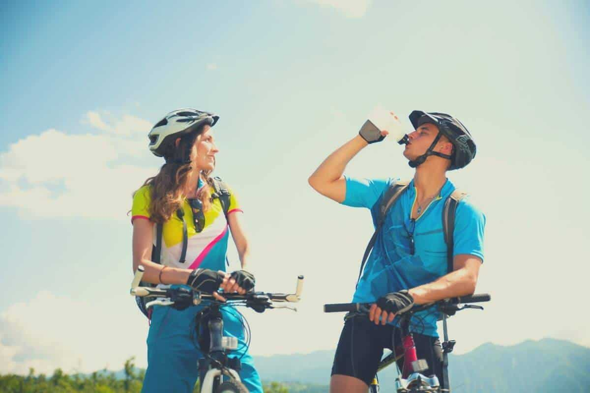 Couple cycling together and man drinking water