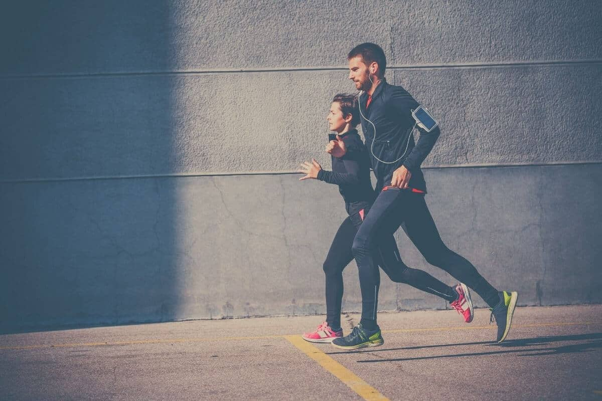 Woman and man running along the pavement